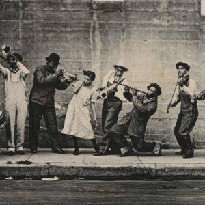 King Oliver's Band in New Orleans, ca. 1921. Ram Hall, Honore Dutrey, King Oliver, Lil Hardin, David Jones, Johnny Dodds, James Palao, & Ed Garland on the sidewalk