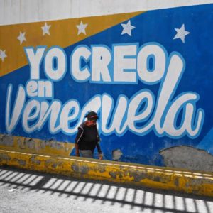 """A woman wearing a face mask walks past a painted wall that reads """"I believe in Venezuela"""" in Caracas, on January 5, 2021. - The new Venezuelan parliament was sworn this Tuesday with President Nicolas Maduro's party now in almost complete control and Western-backed opposition leader Juan Guaido out in the political cold. (Photo by Federico PARRA / AFP) (Photo by FEDERICO PARRA/AFP via Getty Images)"""